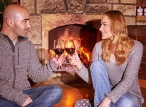 A couple drinking wine in front of their cabin's fireplace.
