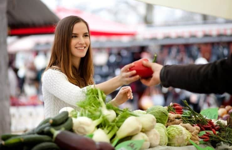 Farmer handing woman a red pepper at the Farmers Market