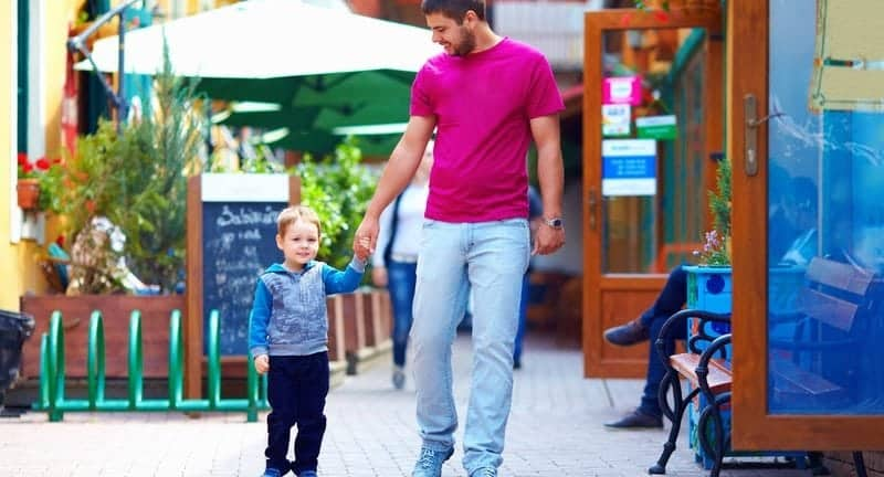 Father and son holding hands walking downtown in small town