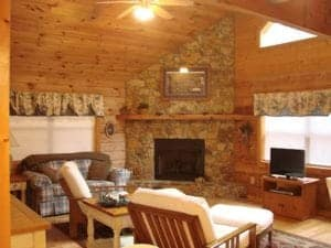 A living room with a stone fireplace at a Murphy North Carolina cabin rental.