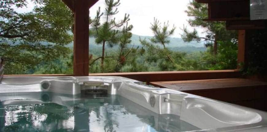 hot tub on deck of one of best cabins in north carolina