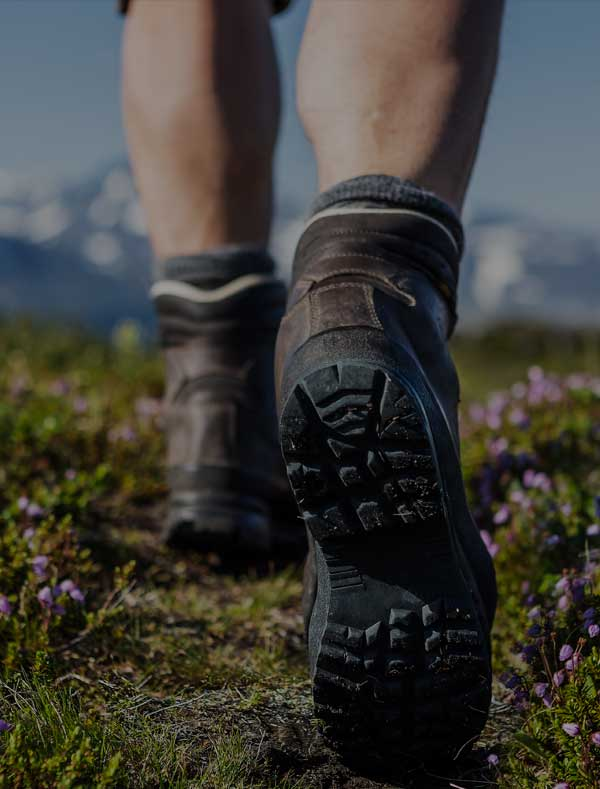 Closeup of someone wearing hiking boots in the mountains.
