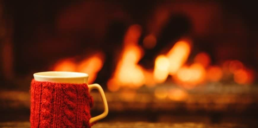 A mug with a wool koozie on a table in front of the fireplace.