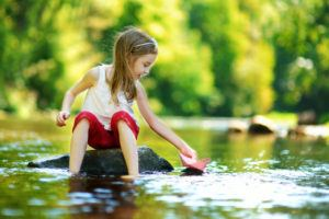 Little girl playing with a paper boat in a river.