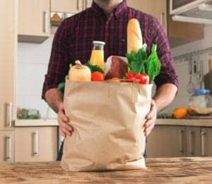 man with paper grocery bag full of food