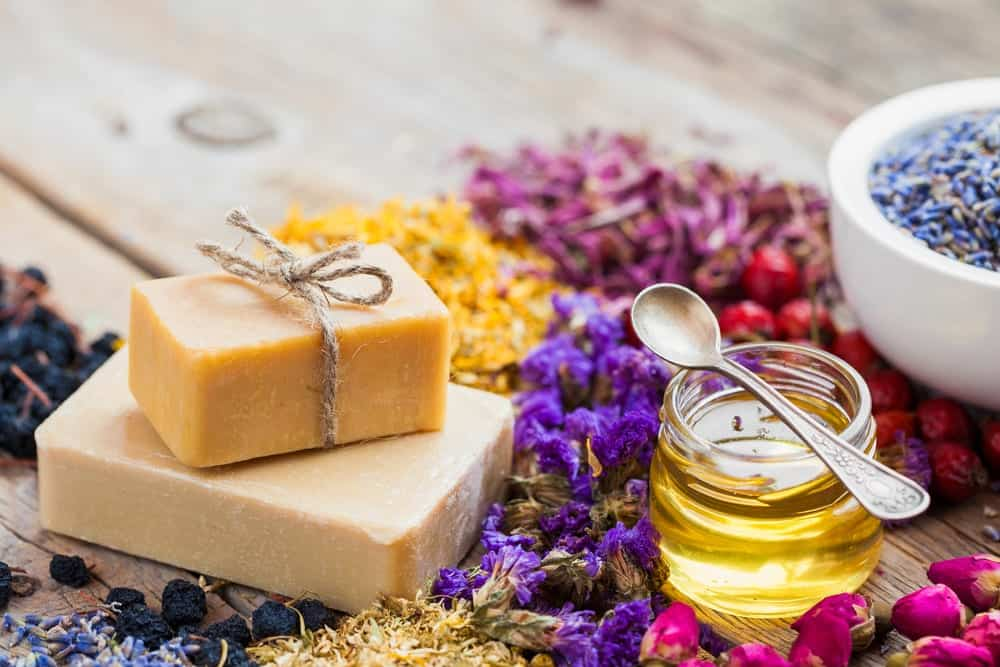 homemade soap next to honey and flowers